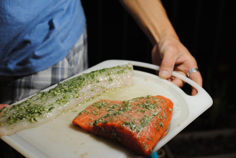 The Grillmaster displaying cuts of true cod (low-amine) and salmon (high-amine) marinating in garlic, dill, and ascorbic acid.